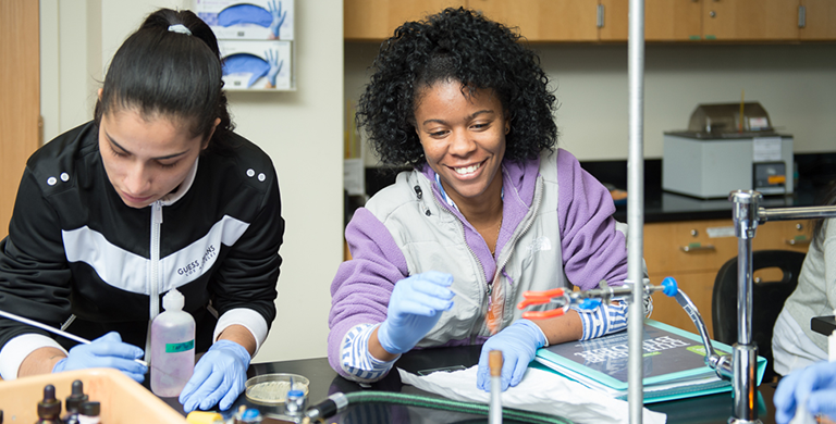 Quincy College Biology Students using bunsen burners in a lab.